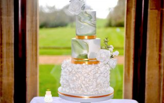 Marbling of green and white with gold accent wedding cake