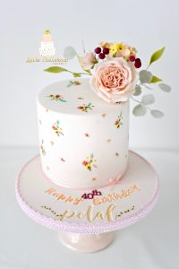 Hand painted cake adorned with sugar flowers