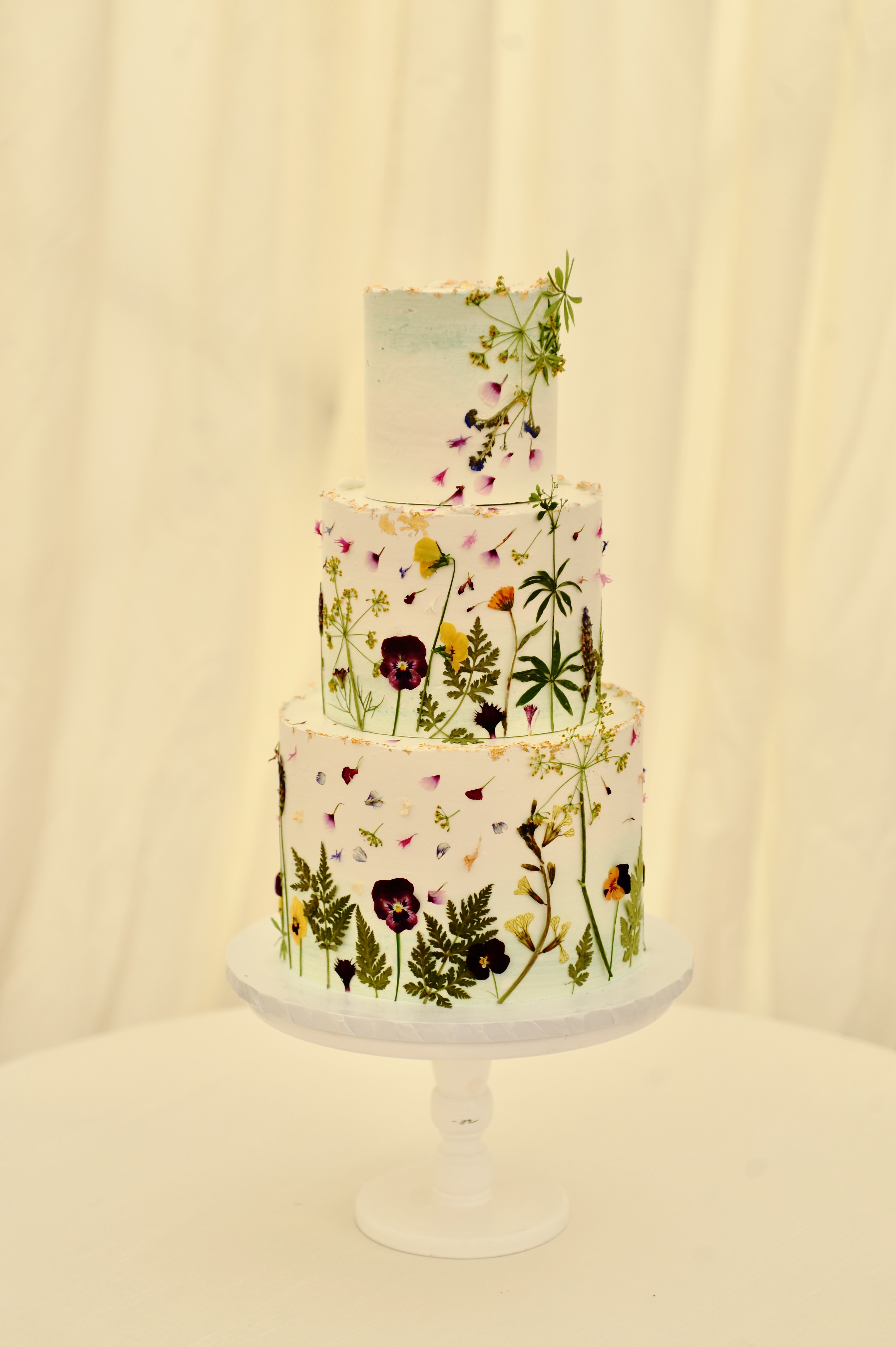 Buttercream cake with pressed organic edible flowers and gold leaf